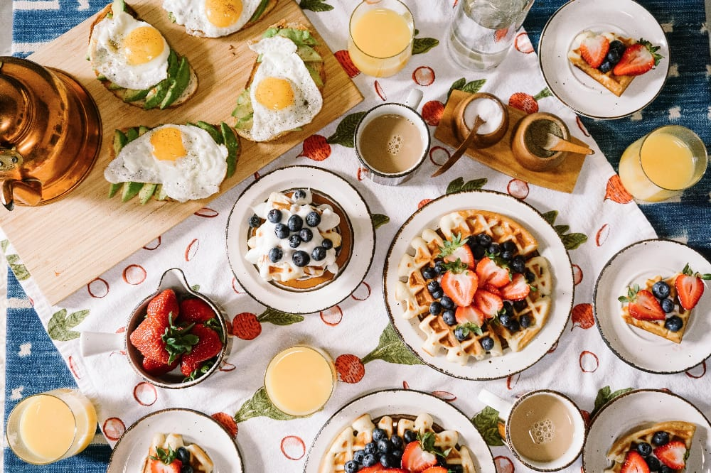 Photo of brunch table with eggs and waffles. Photo by Rachel Park on Unsplash.